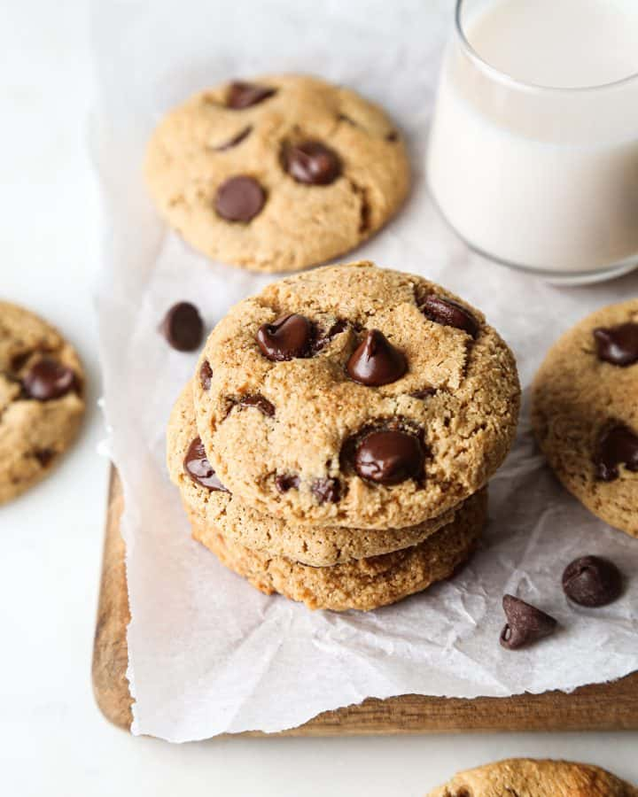 stack of 3 Paleo Chocolate Chip Cookies with other cookies around it and a glass of milk