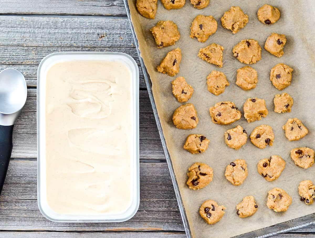 overhead view of a rectangular freezer dish with the lid off full of paleo vanilla ice cream with the baking sheet of frozen paleo cookie dough chunks next to it.