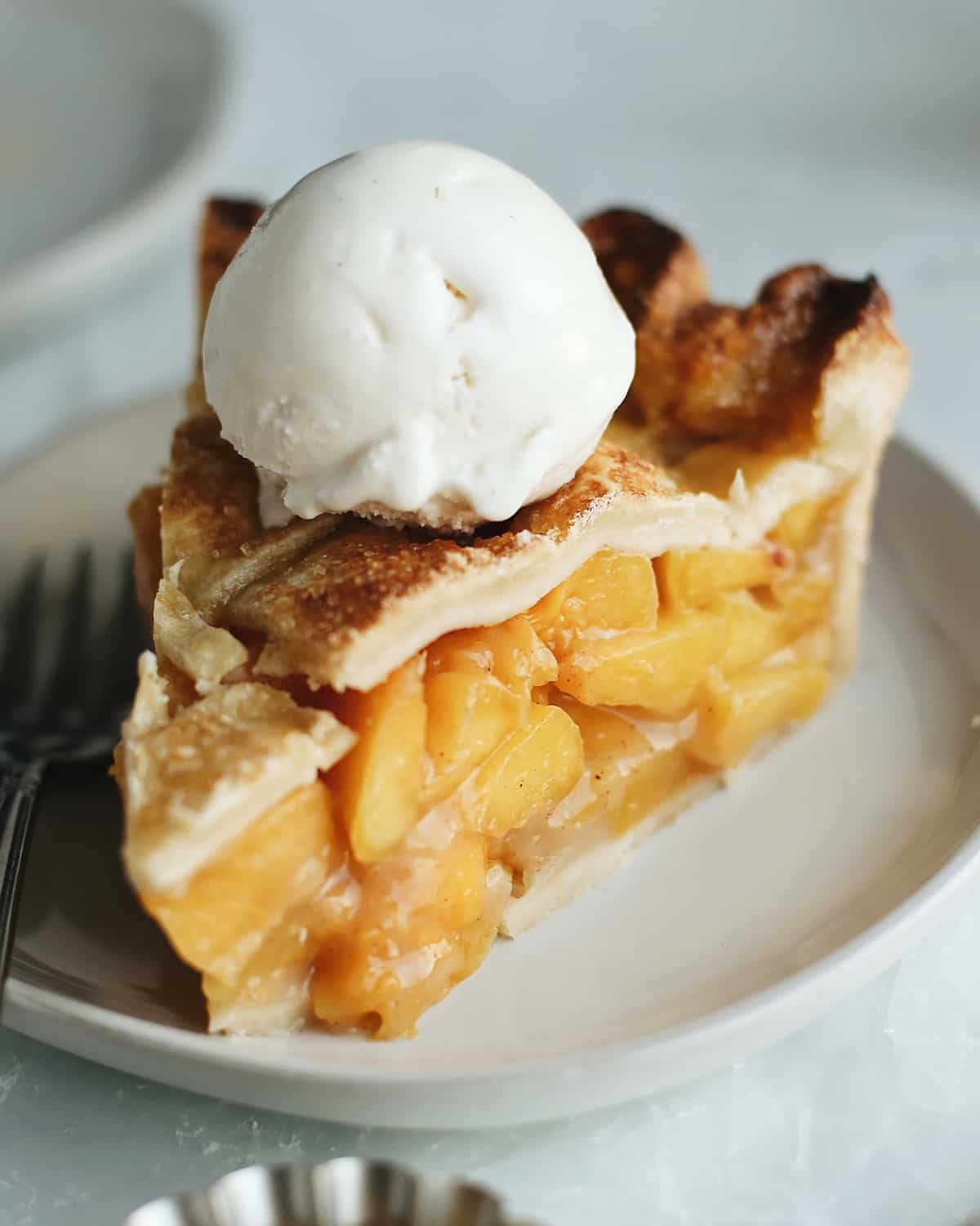 a piece of Fresh Peach Pie on a plate with a scoop of vanilla ice cream on top