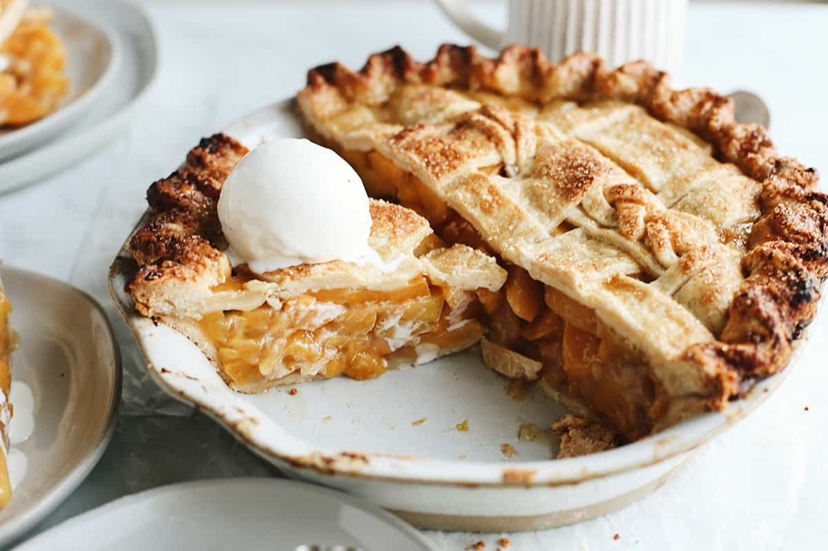 front view of a peach pie in a pie dish with a slice cut out with ice cream on top