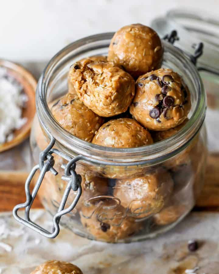 peanut butter energy balls in a glass jar, the top one has a bite taken out of it