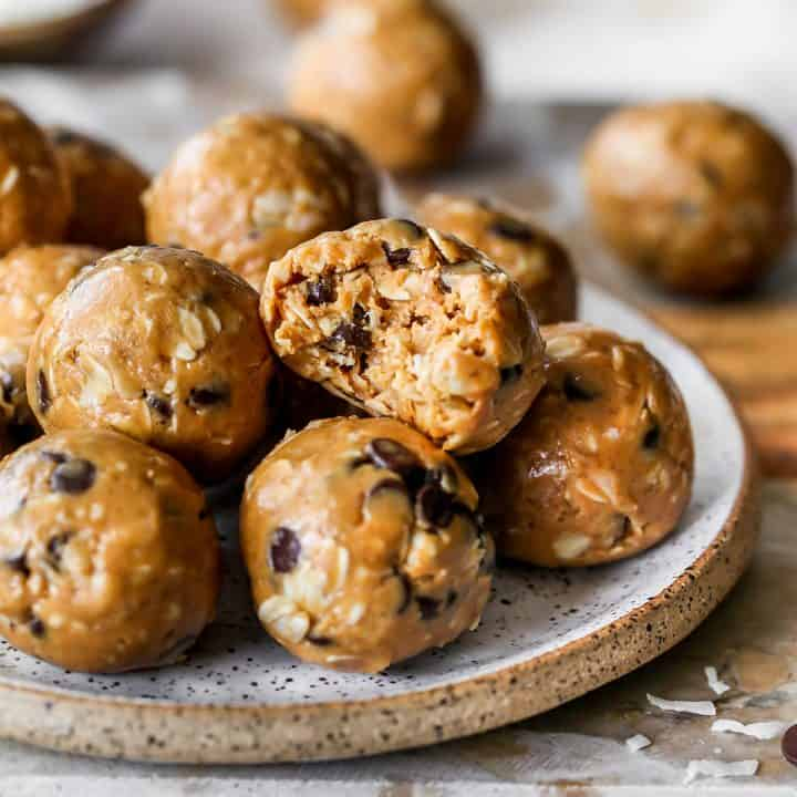 8 peanut butter protein balls stacked on a plate, the top one has a bite taken out of it