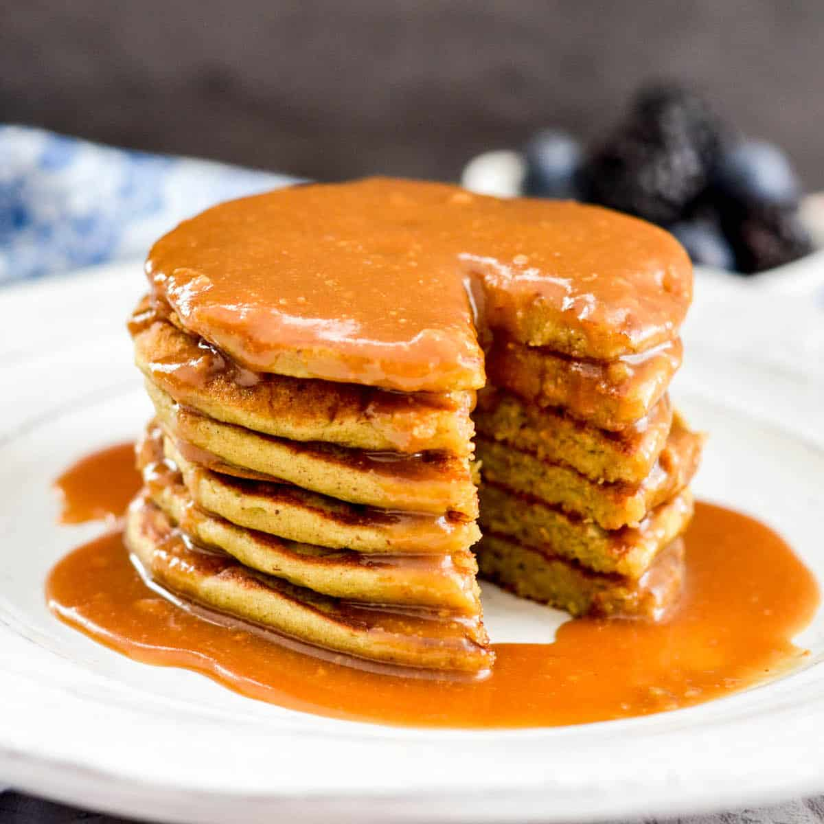 A stack of six Zucchini Banana Pancakes with a bite taken out of it