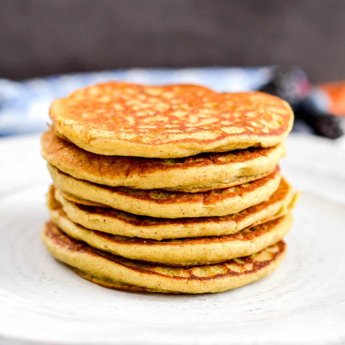 6 stacked zucchini banana pancakes on a plate.