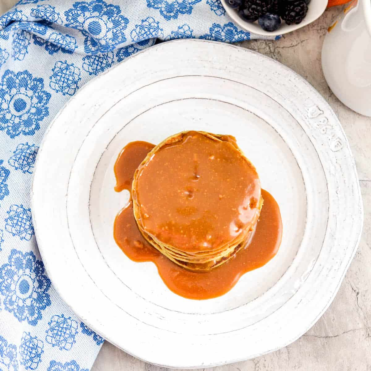 Overhead view of a stack of Zucchini Banana Pancakes with maple syrup.