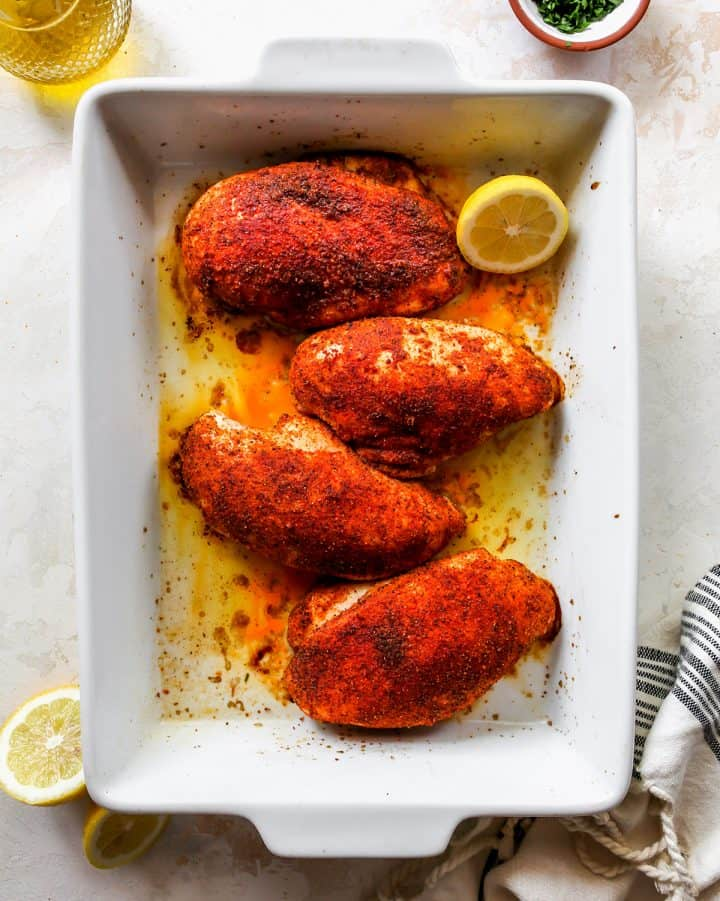overhead view of four Baked Chicken Breasts in a white baking dish.
