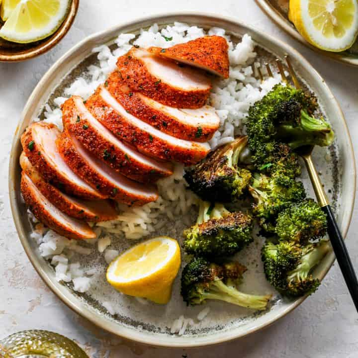 overhead view of a Baked Chicken Breast sliced on top of rice with a side of broccoli on a plate
