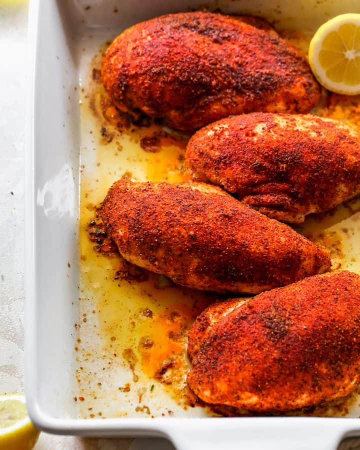 up close overhead photo of 4 Baked Chicken Breasts in a baking dish with lemon