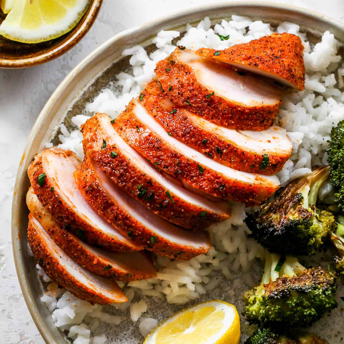 up close overhead view of a Baked Chicken Breast sliced on top of rice with a side of broccoli on a plate