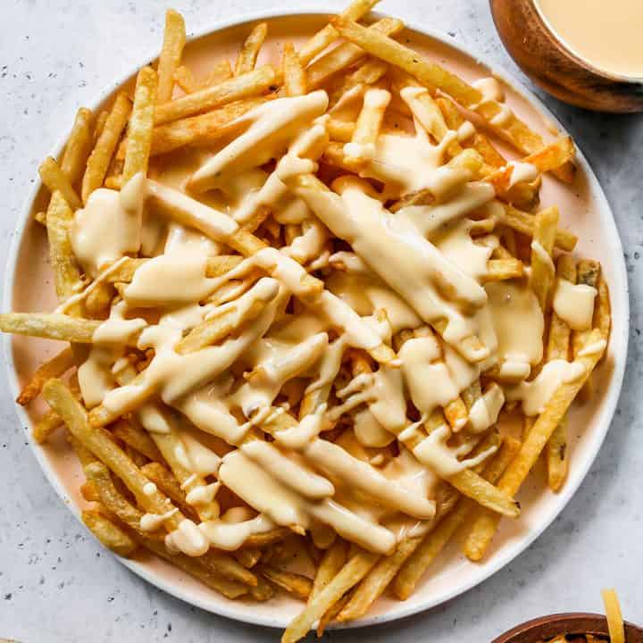 overhead photo of a plate of French fires drizzled with Cheese Sauce