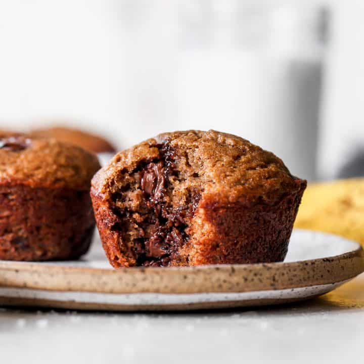 front view of a Healthy Banana Muffin on a plate with a bite taken out of it and another muffin next to it