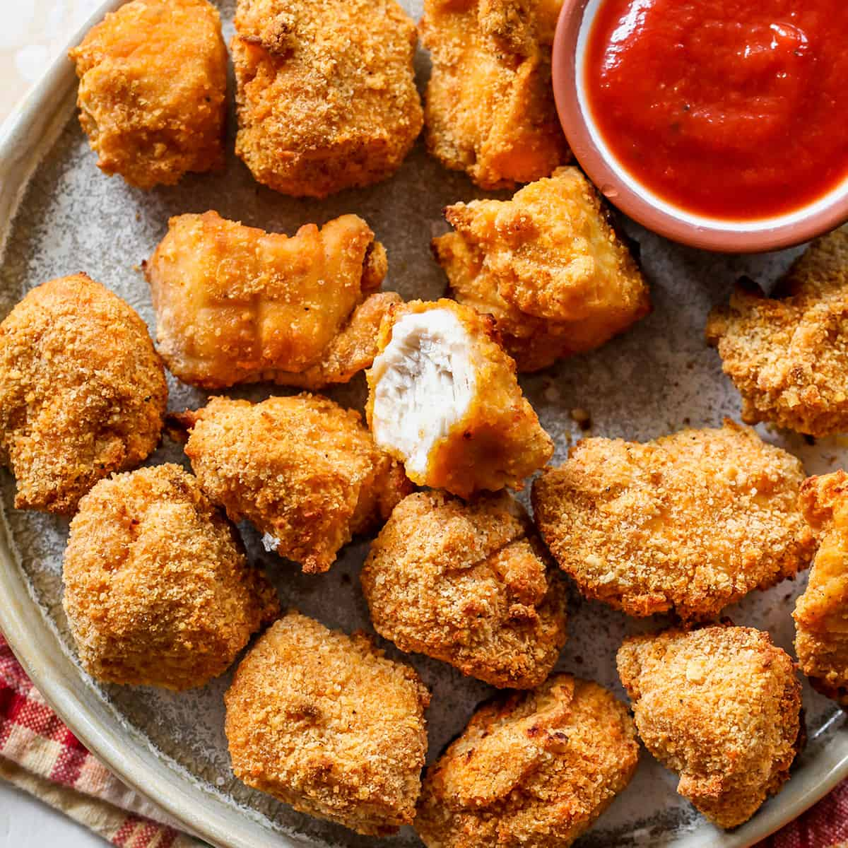 overhead view of Homemade Chicken Nuggets on a plate, one has a bite taken out of it
