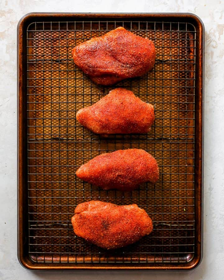 overhead photo showing how to cook chicken breasts in the oven - breasts coated with spice mixture on a wire rack on a baking sheet