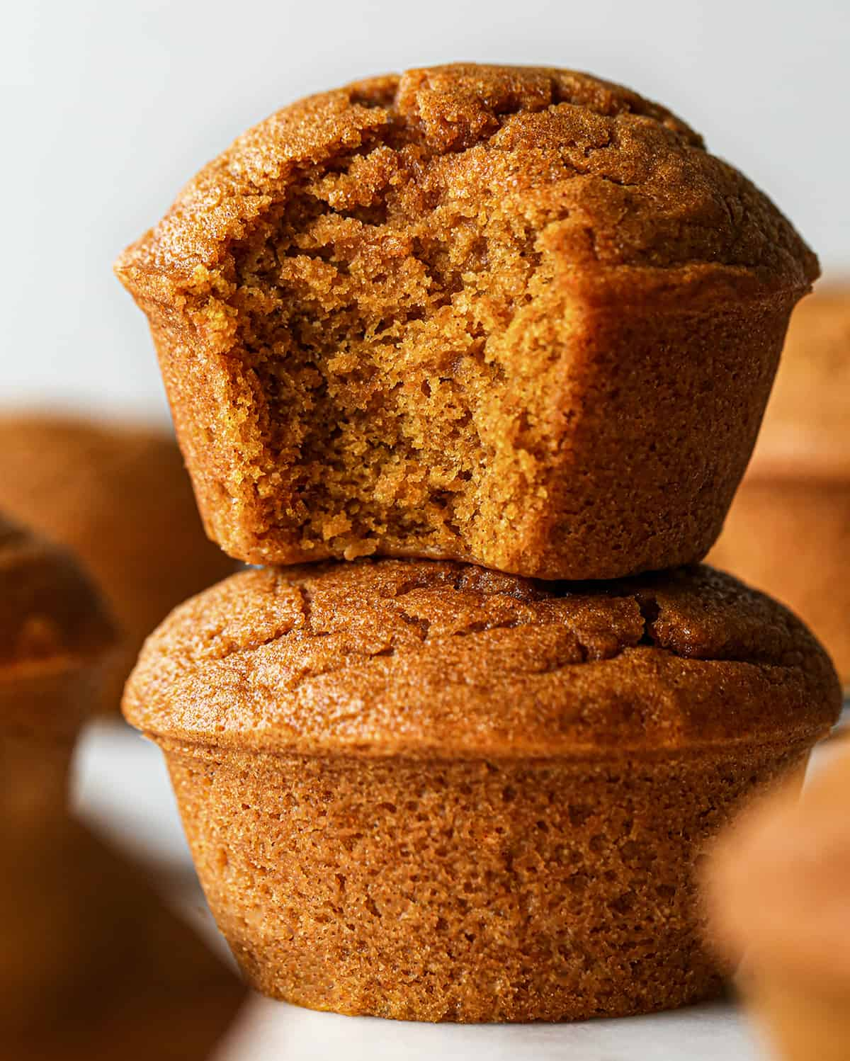 a stack of two Pumpkin Muffins, the top one has a bite taken out of it