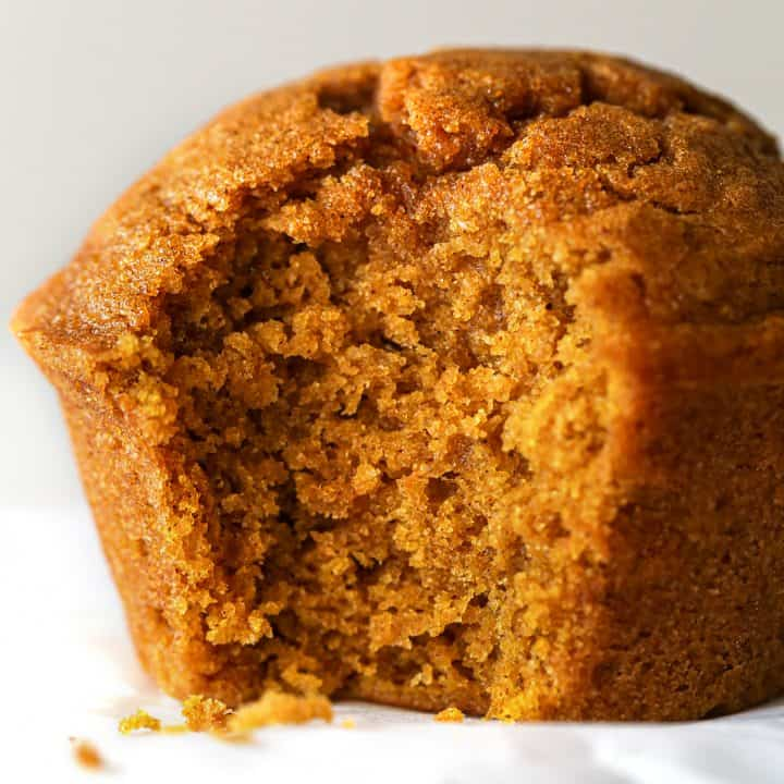 up close photo of a pumpkin muffin with a bite taken out of it