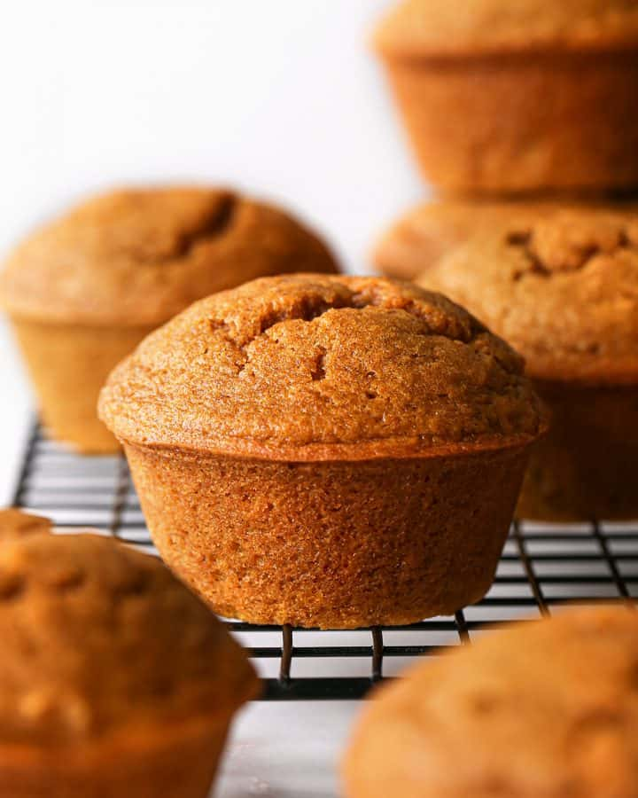 front view of a Pumpkin Muffin on wire cooling rack with other muffins around it