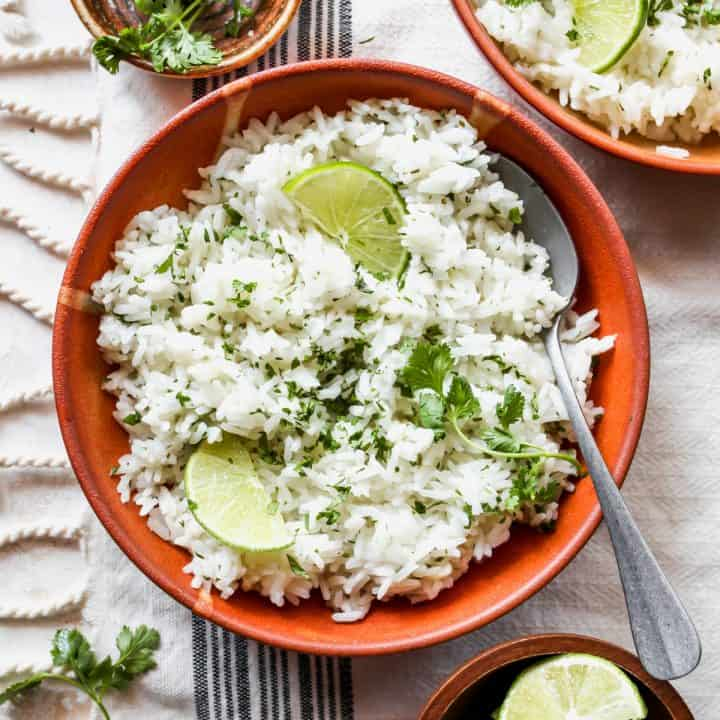 overhead view of a bowl of Cilantro Lime Rice garnished with cilantro and limes with a spoon in it