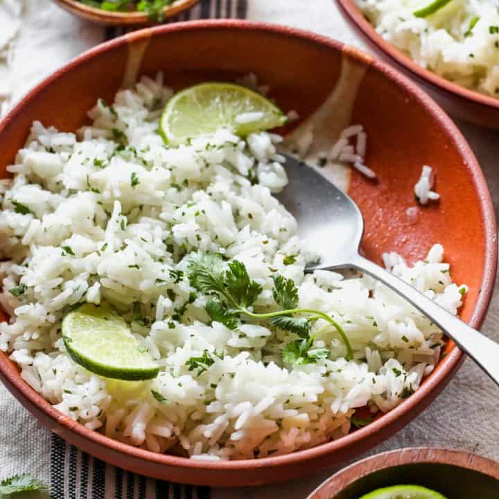 front view of a bowl of Cilantro Lime Rice garnished with cilantro and limes