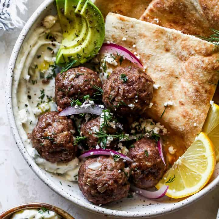 overhead view of Greek Meatballs in a bowl with tzatziki, pita, red onion, fresh dill and feta cheese