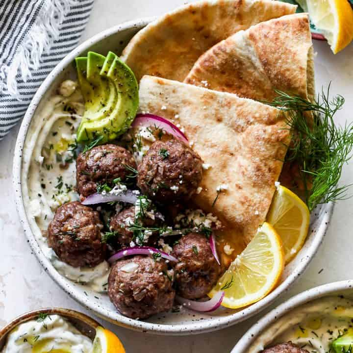 overhead view of Greek Meatballs in a bowl with tzatziki, pita, red onion, fresh dill, avocado and feta cheese