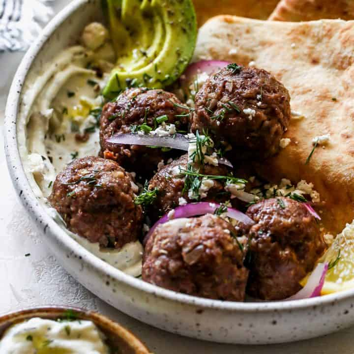 font view of Greek Meatballs in a bowl with tzatziki, pita, red onion fresh dill, avocado and feta cheese