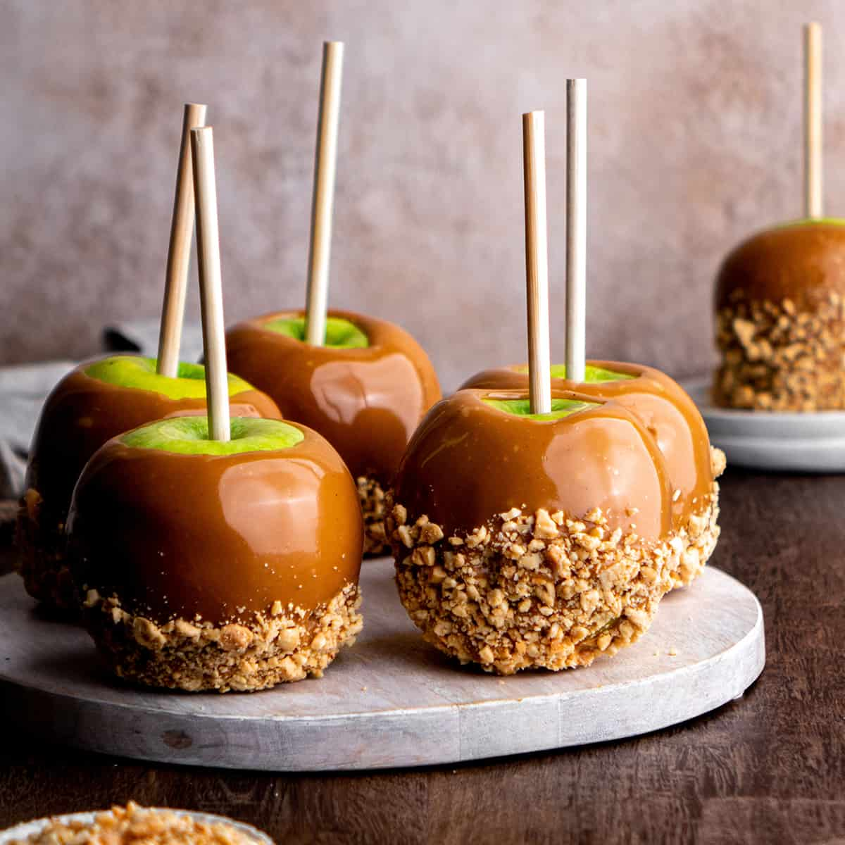 front view of 6 Homemade Caramel Apples with crushed peanuts on a serving board