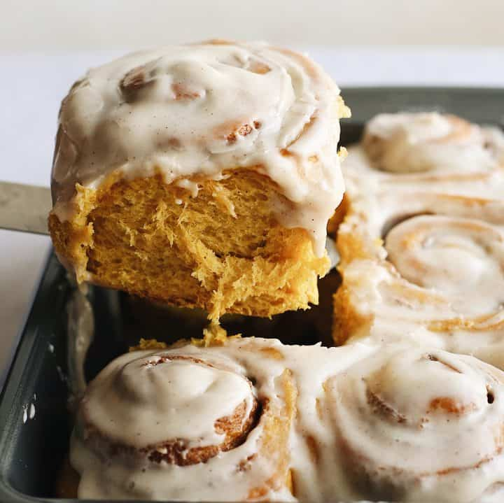 a Pumpkin Cinnamon Roll being lifted out of the pan with a spatula