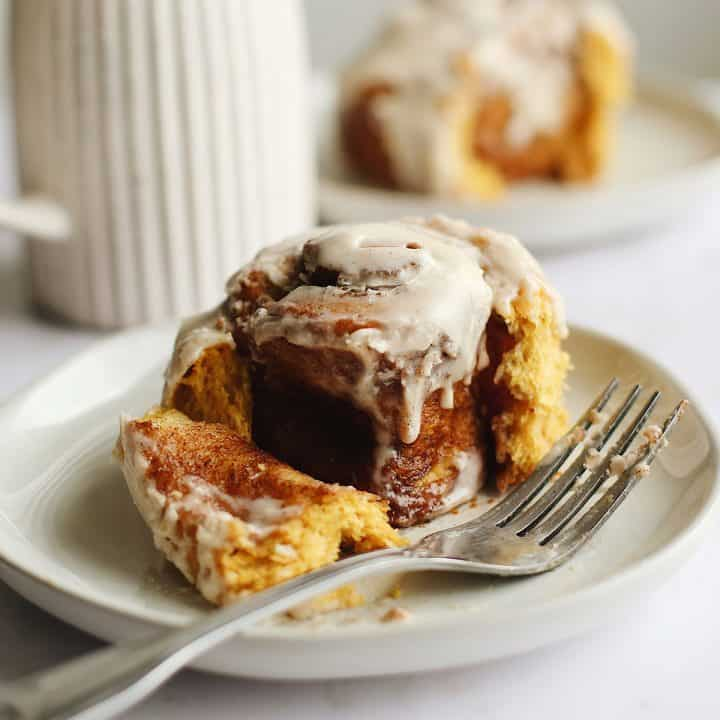 front view of a Pumpkin Cinnamon Roll on a plate with a fork