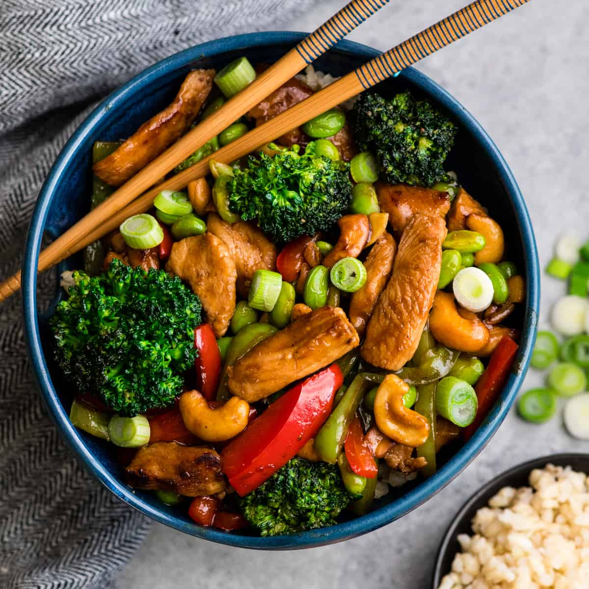 Overhead view of Cashew Chicken Stir Fry Recipe in a blue bowl with chopsticks
